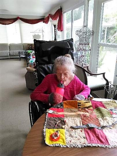 Barbara Enjoying Working with Her Memory Task Blanket in Our Oversized Florida Room